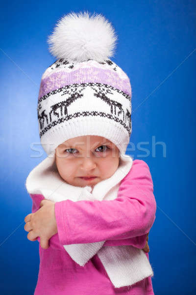 Portrait of an angry baby girl wearing a knit pink and white winter hat. Stock photo © alexandkz