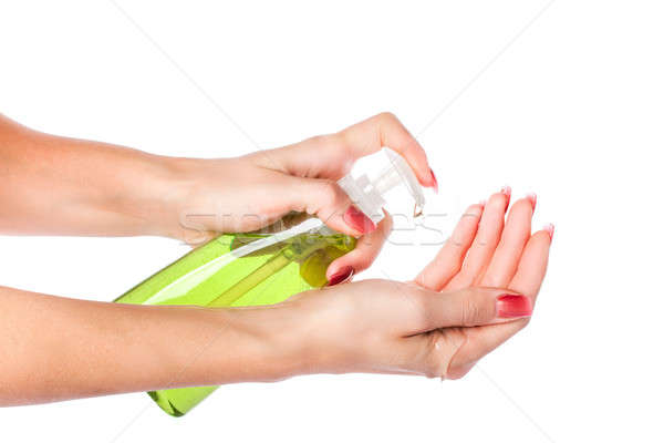 Female hands using hand sanitizer gel pump dispenser. Isolated on white background Stock photo © alexandkz