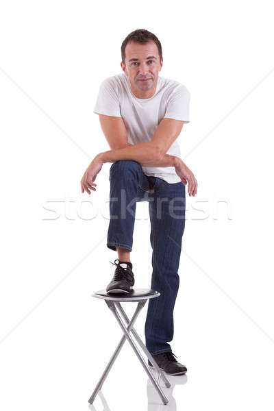 Portrait of a handsome middle-age man with his foot on a bench, on white background. Studio shot Stock photo © alexandrenunes