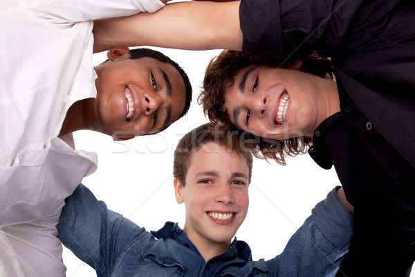 three young man of different colors,looking to camera and smiling, view from below Stock photo © alexandrenunes