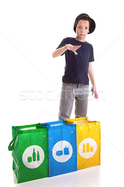 Stock photo: boy putting a plastic bottle to recycle