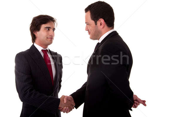 Stock photo: two businessmen shaking hands, and one businessman with his fingers crossed behind his back and smil