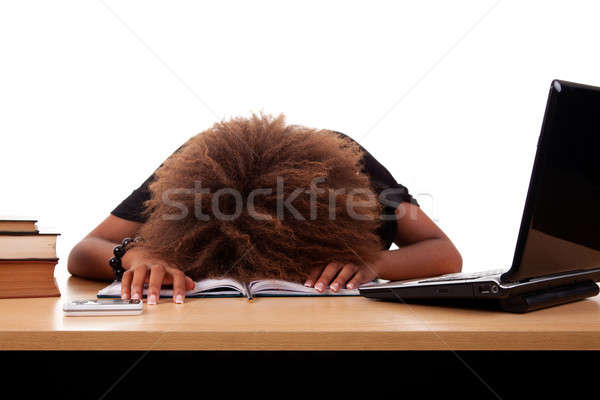 Stressed young black woman, sitting at a table among books and laptop Stock photo © alexandrenunes