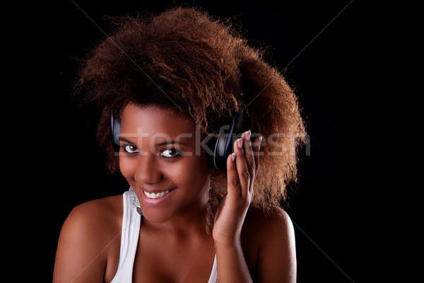 Beautiful black woman happy listening music in headphones Stock photo © alexandrenunes