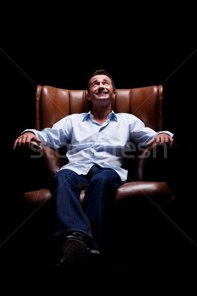 Stock photo: Man smiling and looking up seated on a chair
