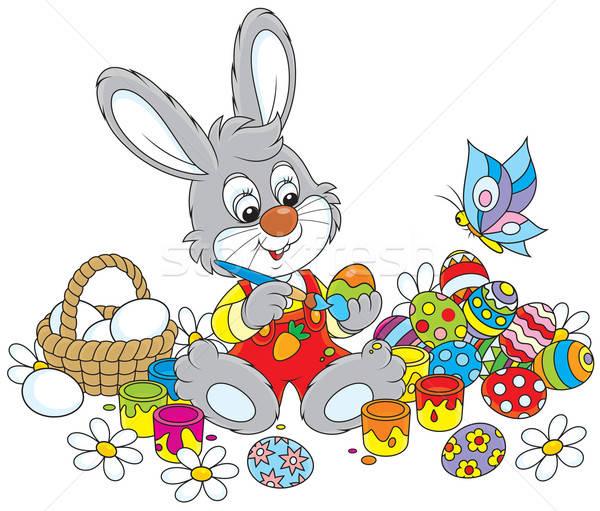 Little Bunny paints Easter eggs Stock photo © AlexBannykh