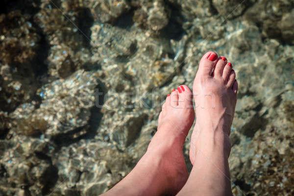 Woman's feet over water Stock photo © alexeys