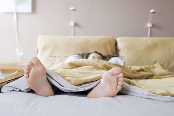 Reggel lány ágy fény otthon láb Stock fotó © alexeys