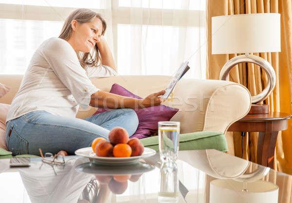 Mulher sofá revista mulher madura relaxante apartamento Foto stock © alexeys