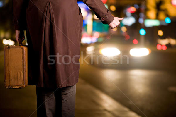 A hitchhiker with an old suitcase is waiting on a sidewalk as ni Stock photo © alexeys