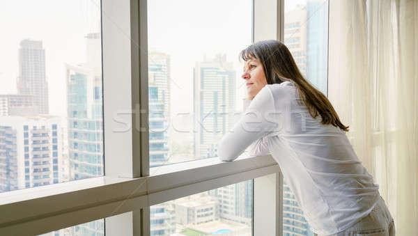 Vida cidade mulher madura olhando fora janela Foto stock © alexeys