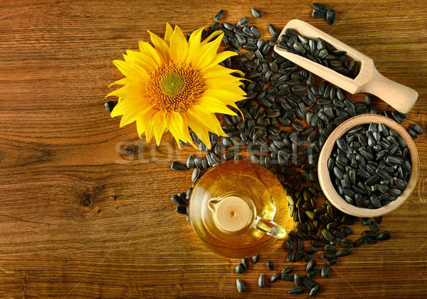 Seeds, oil and sunflower flower on a wooden background Stock photo © alinamd