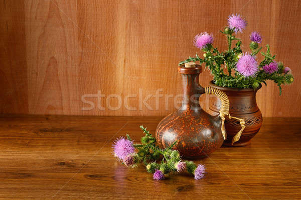 Stock photo: Oil and flower of milk thistle on wooden background.