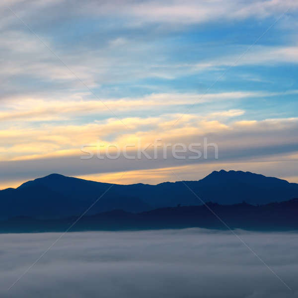 The sunrise, fog and mountain peaks. Stock photo © alinamd