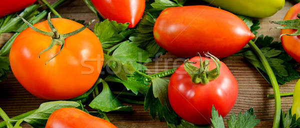 Tomatoes and celery on wooden background. Stock photo © alinamd