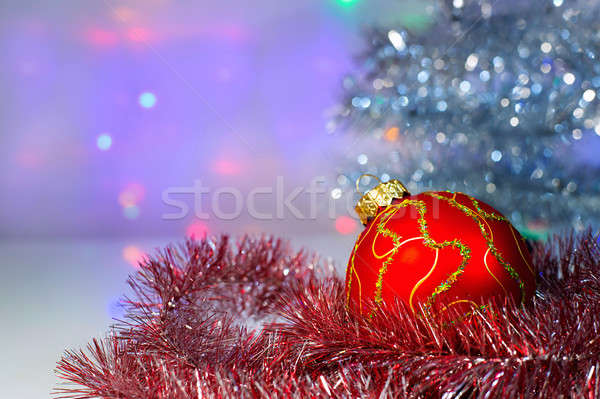 Stock photo: Red Christmas ball under the tree and tinsel
