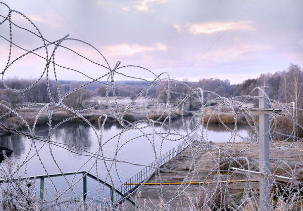 Stock photo: Post a fence of barbed wire in winter in frost at dawn