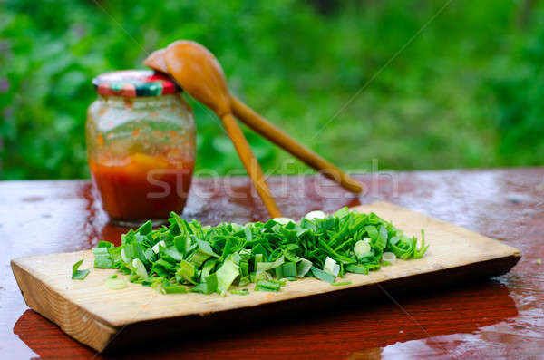 Chopped green onions on a cutting Board, on the background of tw Stock photo © AlisLuch