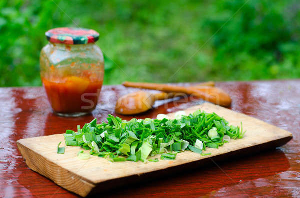 Still life of sliced green onions on a cutting Board, wooden spo Stock photo © AlisLuch
