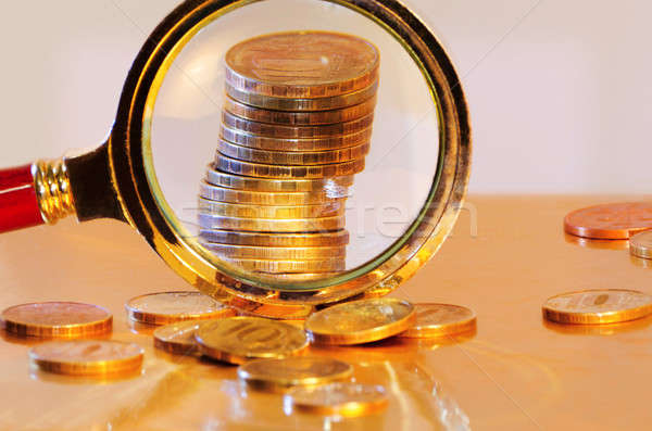 A stack of coins under a magnifying glass Stock photo © AlisLuch