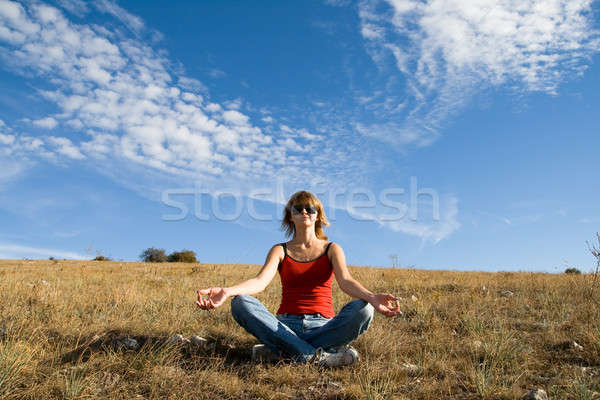 Stock photo: She sits on the ground under a blue sky with clouds and meditate
