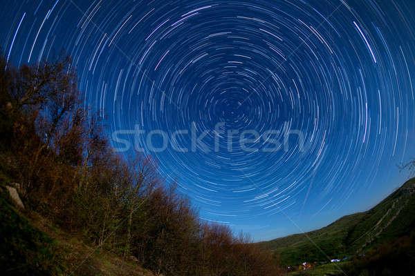 Foto stock: Noite · paisagem · árvores · céu · noturno · em · movimento · estrelas