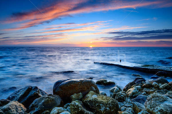 Stock photo: The coastline with stones in the water at sunset