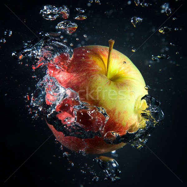 Stock photo: Apple is under water in a stream of air bubbles