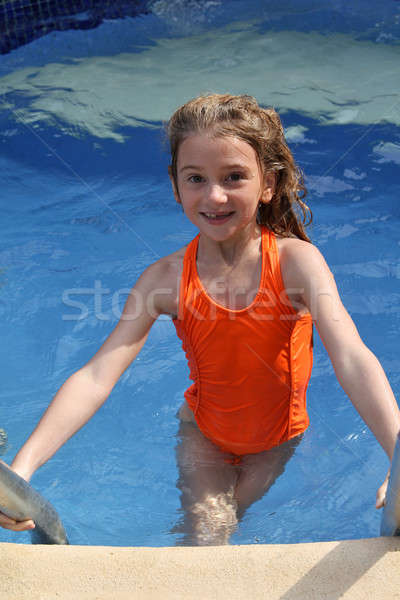 Girl climbing out of pool Stock photo © allihays