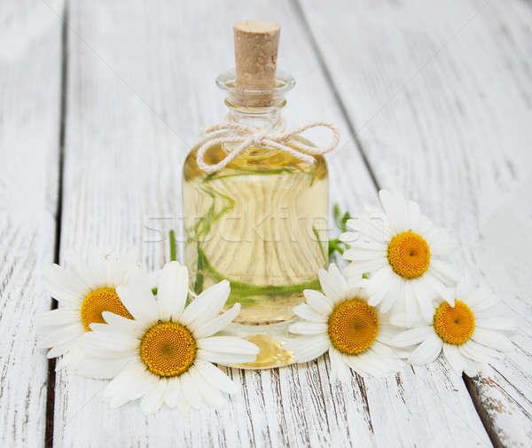 Massage oil and chamomile Stock photo © almaje