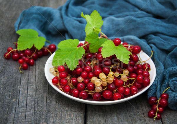 Tányér piros ribiszke öreg fa asztal levél Stock fotó © almaje