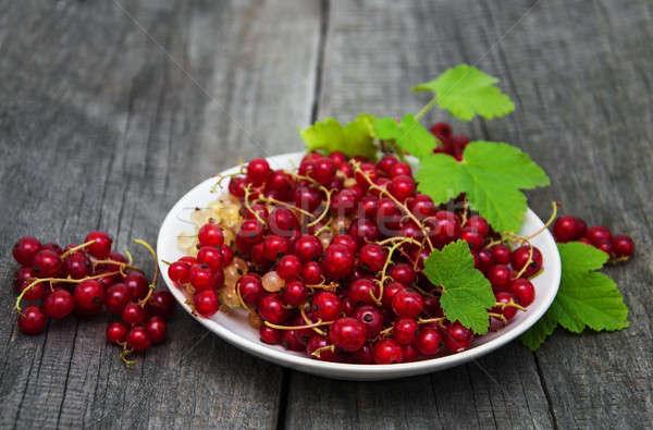 Plaka kırmızı frenk üzümü eski ahşap masa yaprak Stok fotoğraf © almaje