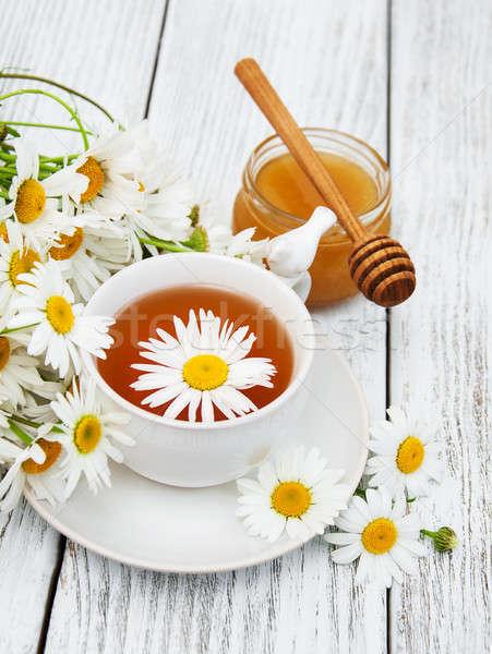 Csésze gyógynövény tea kamilla virágok fa asztal virág Stock fotó © almaje