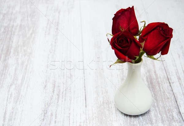 Váza vörös rózsák öreg fából készült textúra fa Stock fotó © almaje