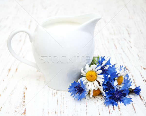 Jug of milk and wildflowers Stock photo © almaje