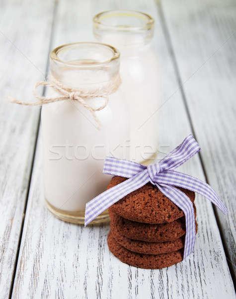 Kása sütik üvegek tej öreg fa asztal Stock fotó © almaje