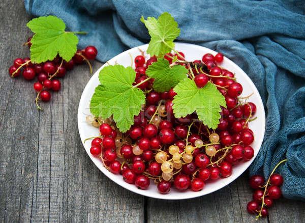 Plaka kırmızı frenk üzümü eski ahşap masa ahşap Stok fotoğraf © almaje