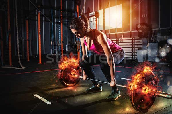 Athletic girl works out at the gym with a fiery barbell Stock photo © alphaspirit