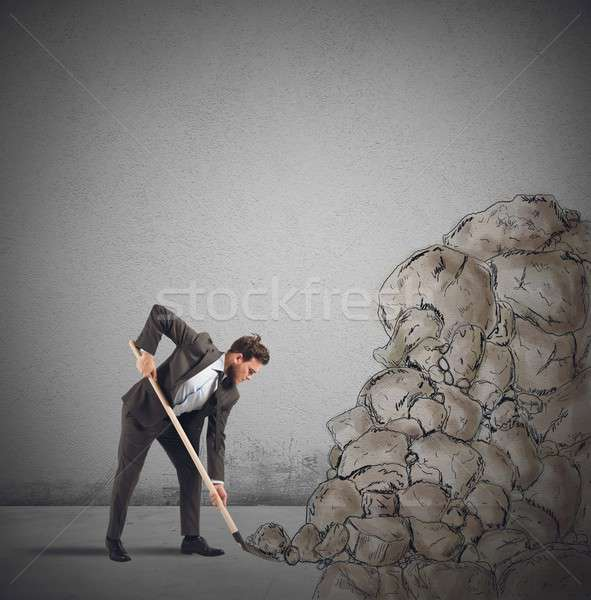 Businessman removes an obstacle rock  Stock photo © alphaspirit