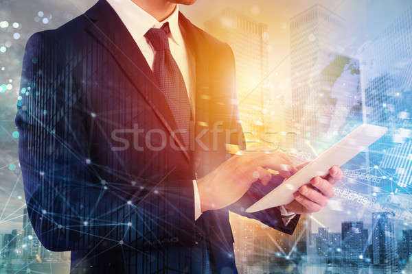 Businessman shares document with tablet. Internet network effect on background Stock photo © alphaspirit