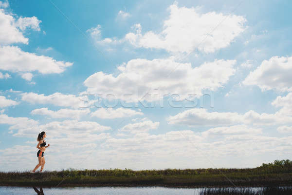 Running girl on a green field and bright sky Stock photo © alphaspirit