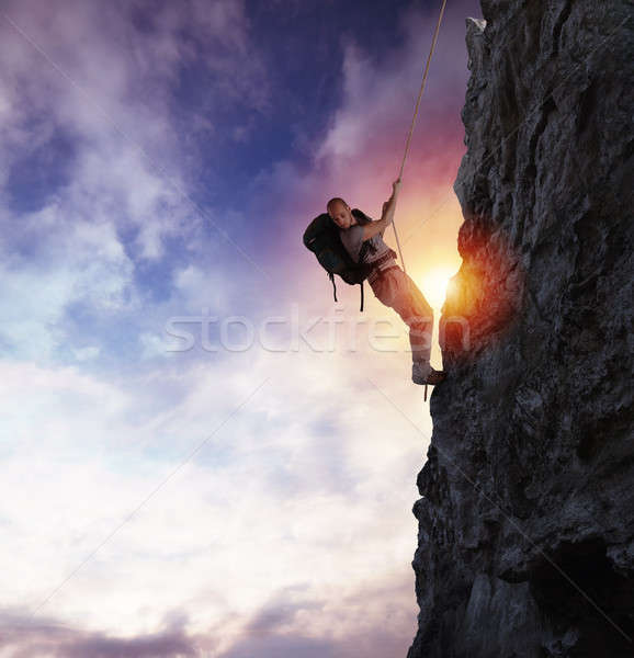 Man climbs a high danger mountain with a rope during sunset Stock photo © alphaspirit