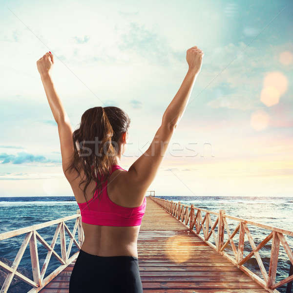 Stretching on a pier in front of sun Stock photo © alphaspirit