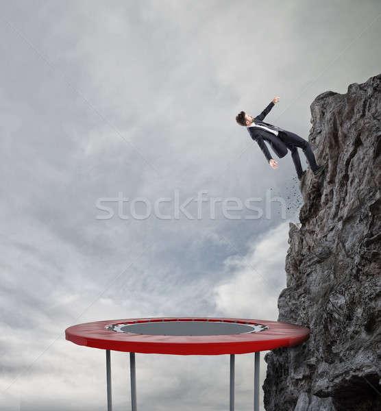 Empresário saltando trampolim alcançar bandeira realização Foto stock © alphaspirit