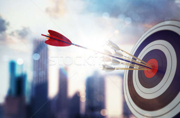 Arrow hit the center of target with modern skyscraper background. Business target achievement concep Stock photo © alphaspirit