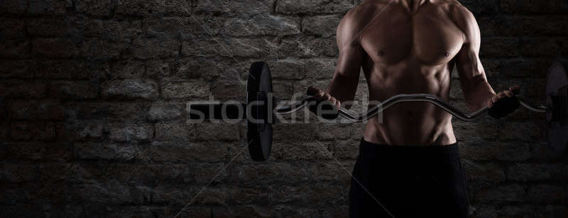 Athletic man training biceps at the gym. to use as banner Stock photo © alphaspirit