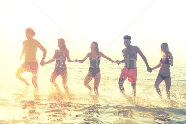 Groep vrienden lopen zee zomertijd Blauw Stockfoto © alphaspirit