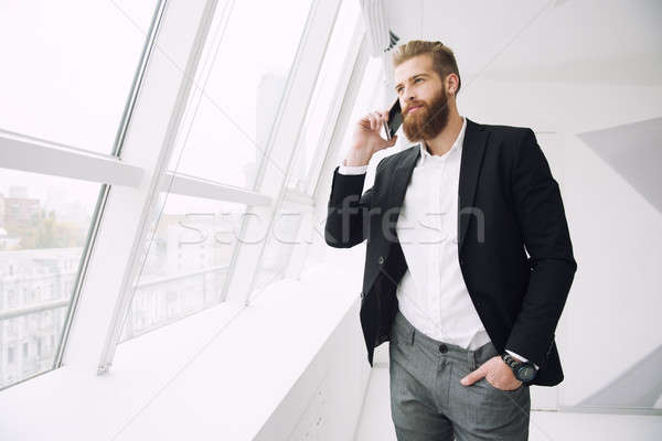 Businessman talking to the phone in office Stock photo © alphaspirit