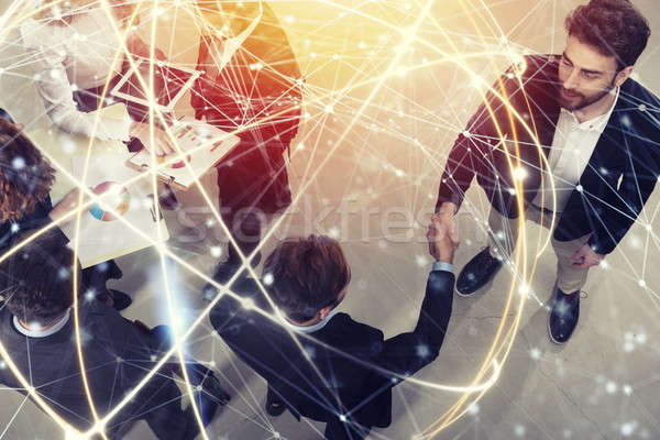 Handshaking business person in office. concept of teamwork and partnership. double exposure with net Stock photo © alphaspirit