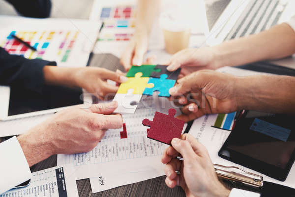 Team of businessmen work together to build a puzzle. Concept of unity and partnership Stock photo © alphaspirit